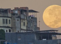 "A ""supermoon"" sets behind the Mare shanty town complex in Rio de Janeiro, Sunday, May 6, 2012. A supermoon is the coincidence of a full moon (or a new moon) with the closest approach the moon makes to the Earth. (AP Photo/Victor R. Caivano)"